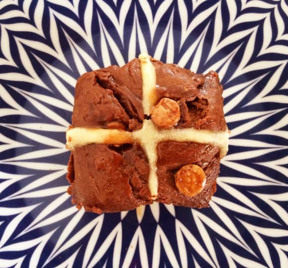 A chocolate chip hot cross bun with a piped cross.