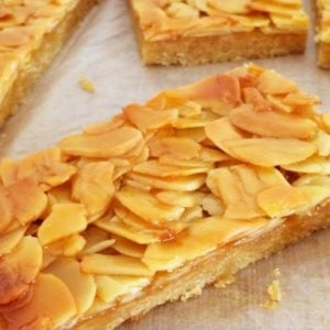 Pieces of slice topped with toasted flaked almonds on a bench