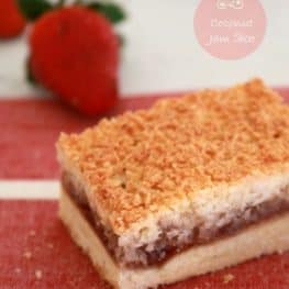 A piece of slice with a base, jam layer and toasted coconut layer on top