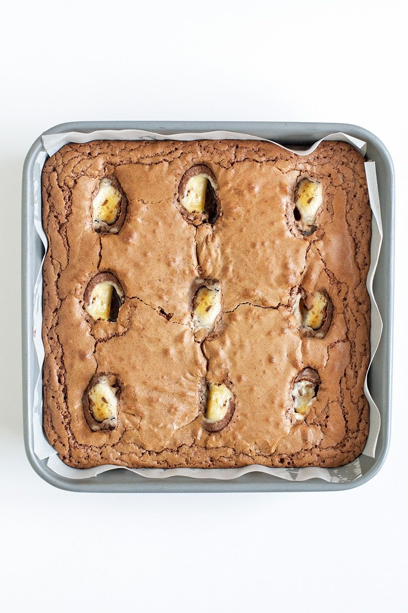 A tray of chocolate brownies with creme eggs inside.