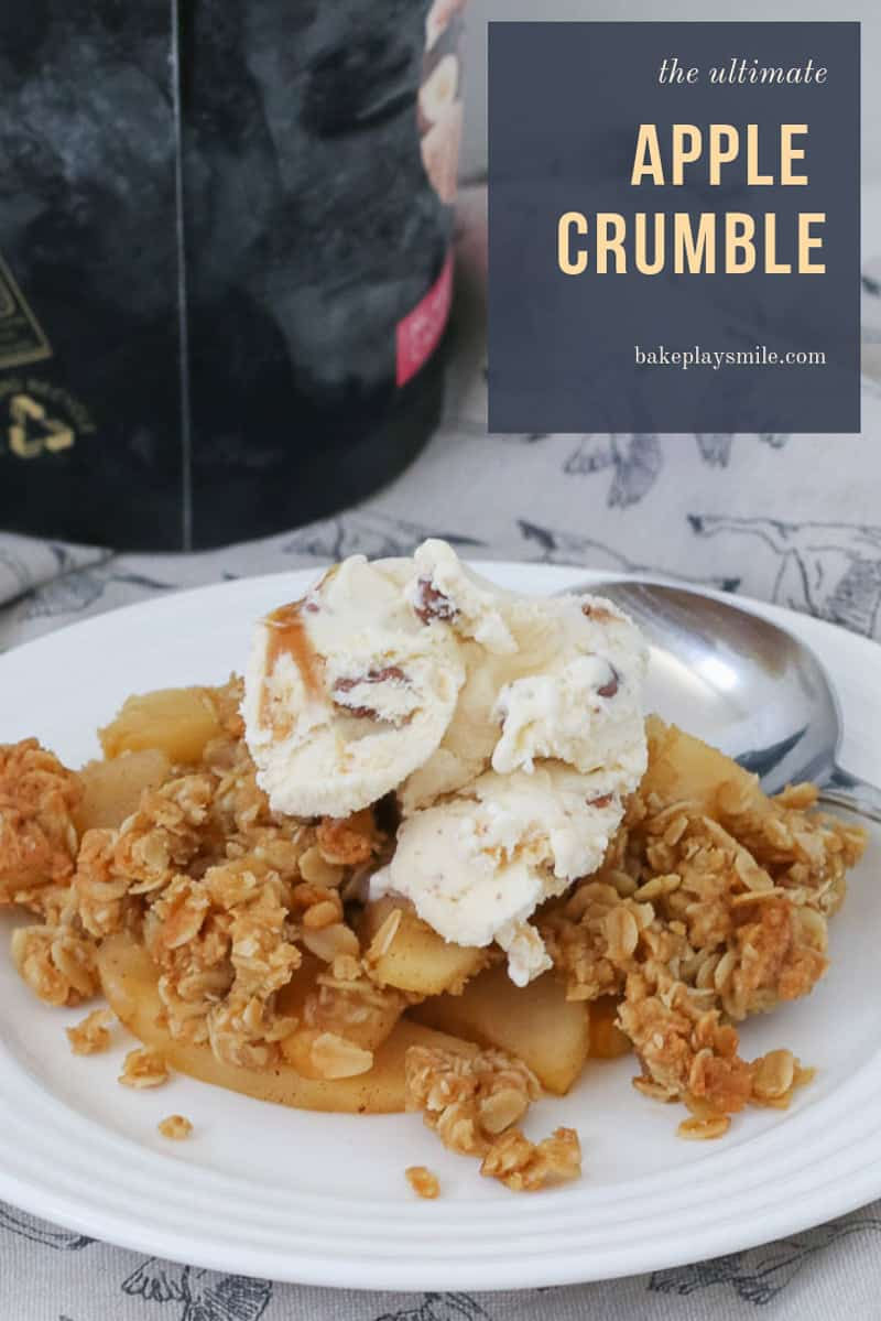 A plate of apple crumble dessert topped with ice cream, on a plate with spoon.