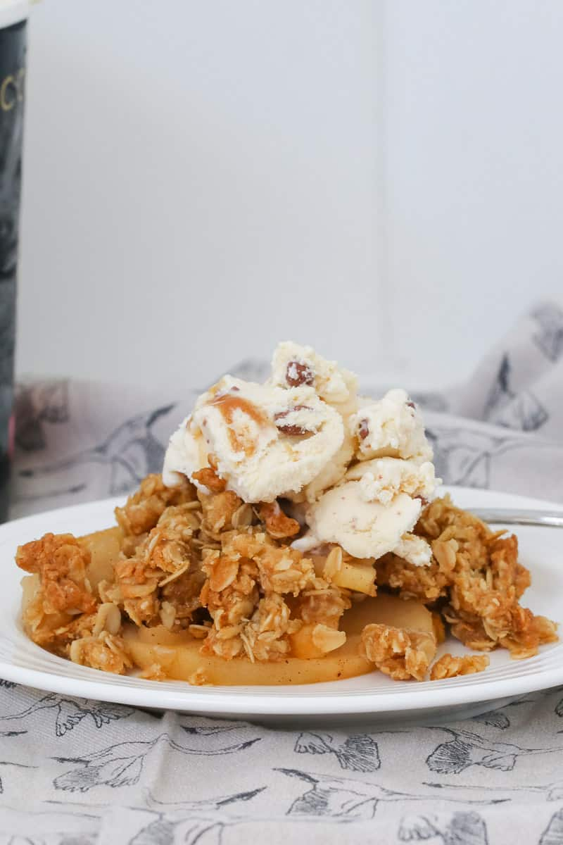 A plate of apple dessert with an oat topping and a scoop of ice-cream.
