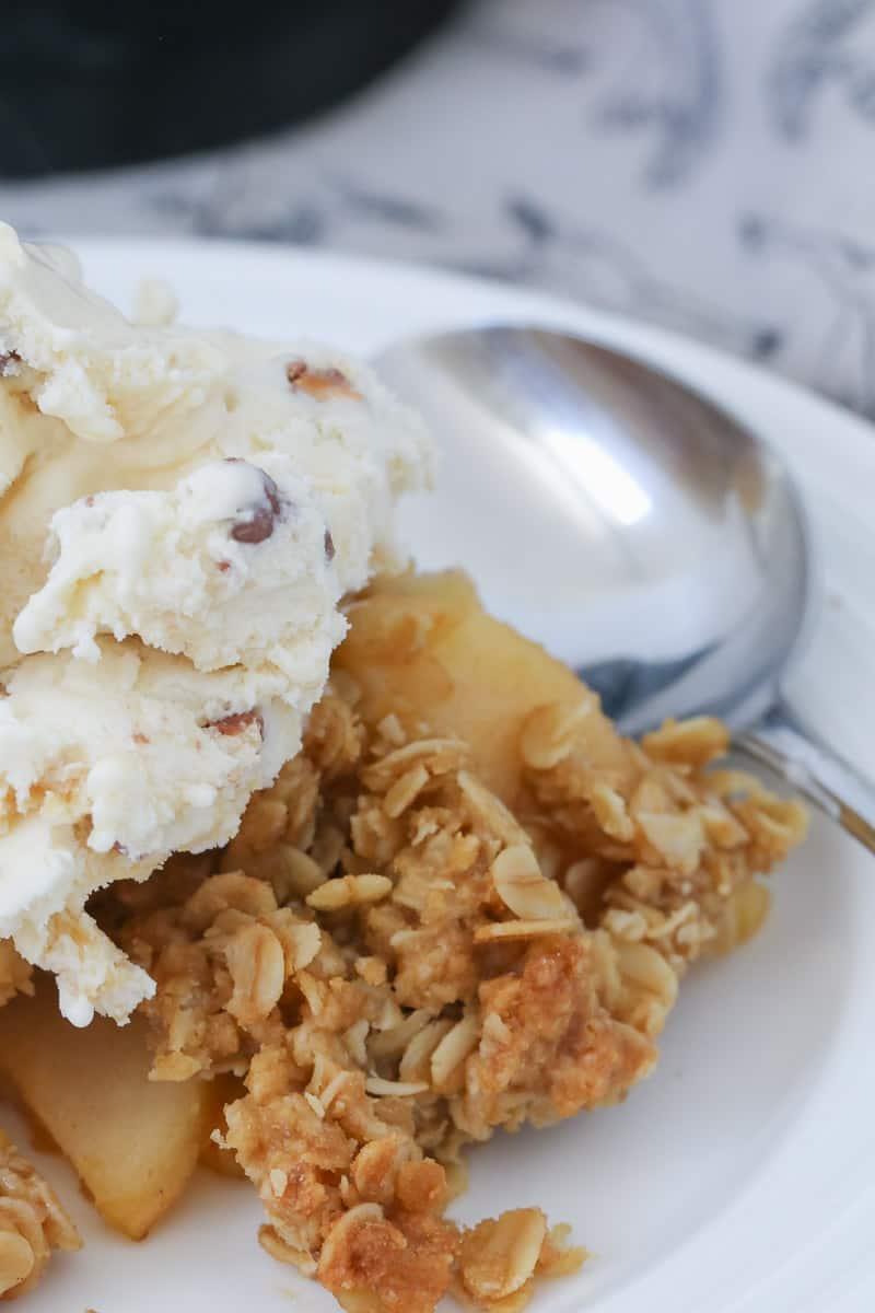 Ice-cream on top of a plate of apple crisp.