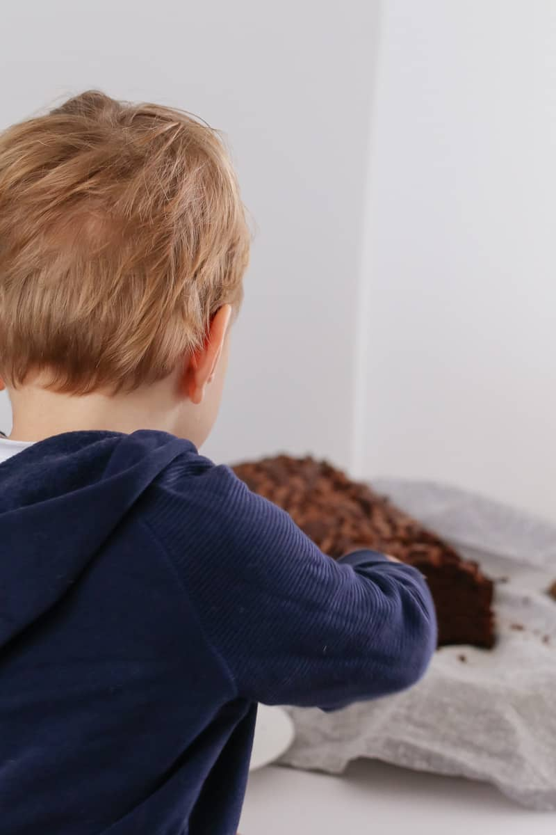 A young boy looking towards a chocolate loaf.