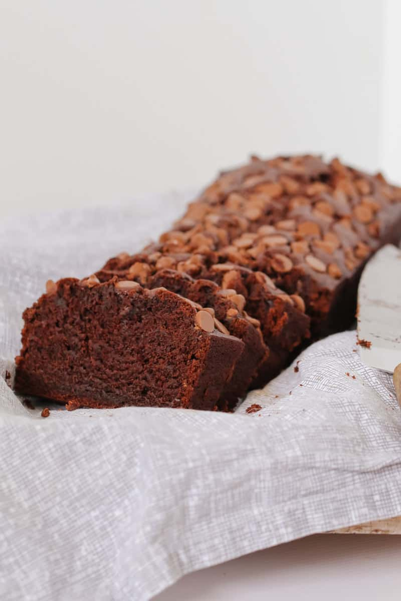 A sliced chocolate loaf topped with milk chocolate bits on a white tea towel.