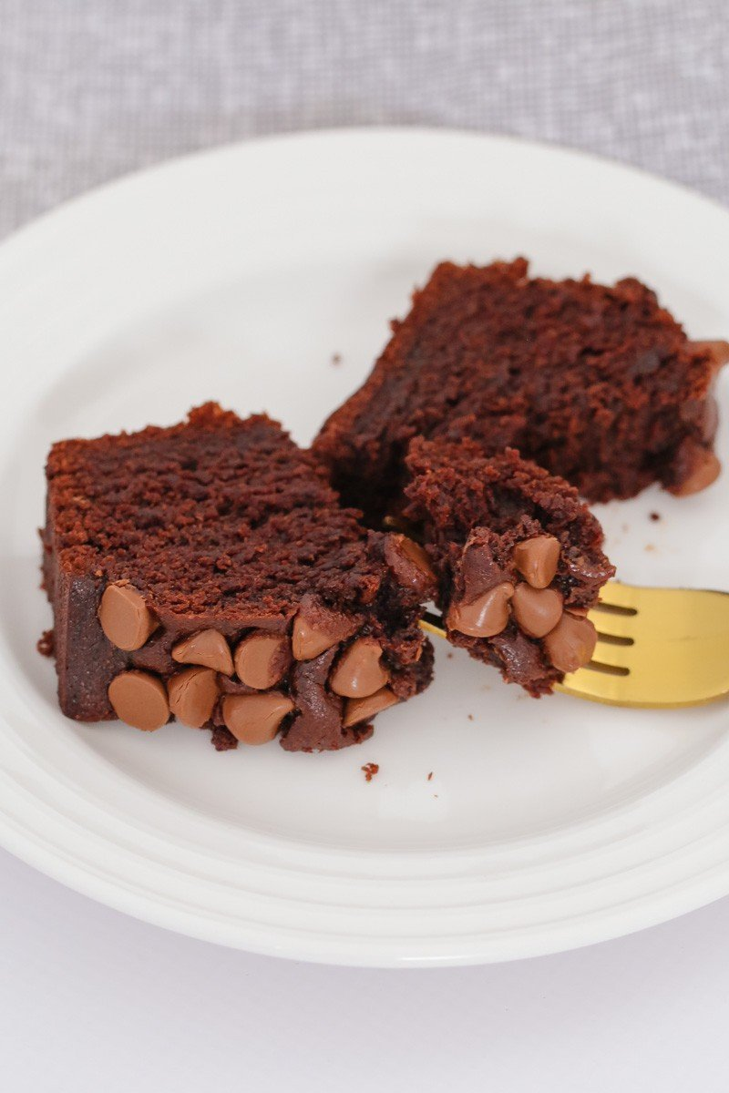 A slice of chocolate loaf topped with milk chocolate bits and a gold fork on a white plate