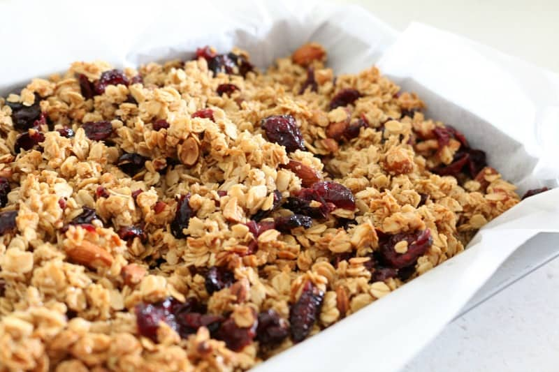 A baking tray lined with baking paper and filled with rolled oats, cranberries and almonds.
