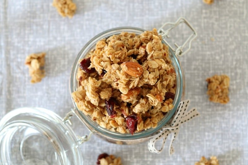 An overhead shot of a glass jar filled with homemade granola made with nuts and dried fruit.