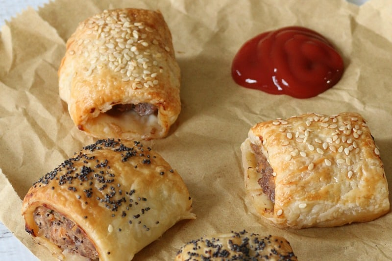 A close up of mini beef sausage rolls, some sprinkled with poppy seeds, and some with sesame seeds