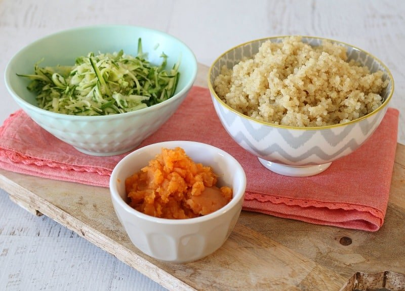 Three individual bowls with ingredients for fritters - grated zucchini, cheesy quinoa and mashed sweet potato
