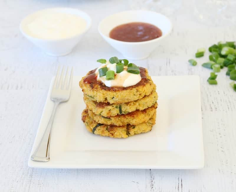 A stack of fritters on a square white plate, with a dollop of sour cream and chives on top, and a bowl of dipping sauce nearby