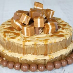 A round mud cake drizzled with caramel sauce and decorated with a pile of Jersey Caramels on top, and Maltesers around the base