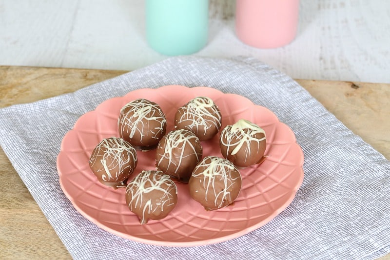Seven chocolate coated cheesecake balls drizzled with white chocolate on a pink plate
