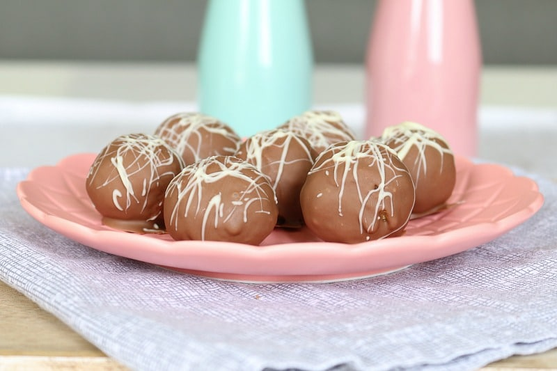 A pink plate with chocolate coated cheesecake balls drizzled with white chocolate on it