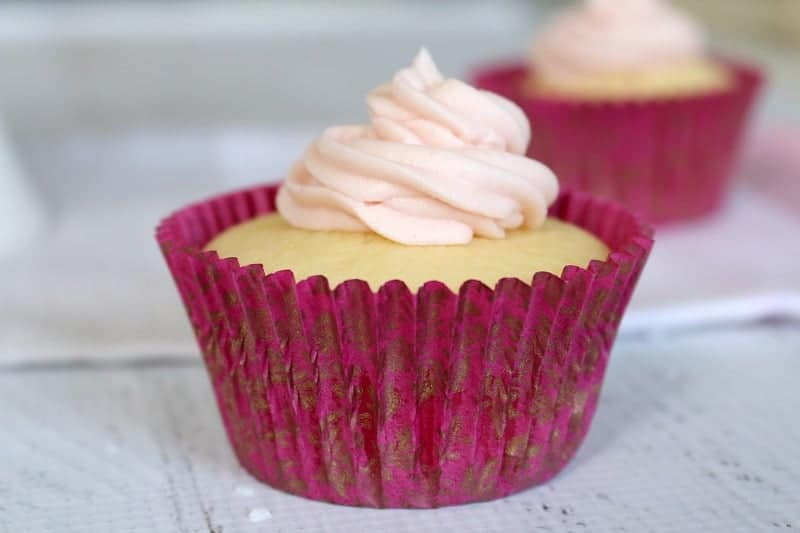 A close up of a lemon cupcake in a pink case with a swirl of white frosting on top