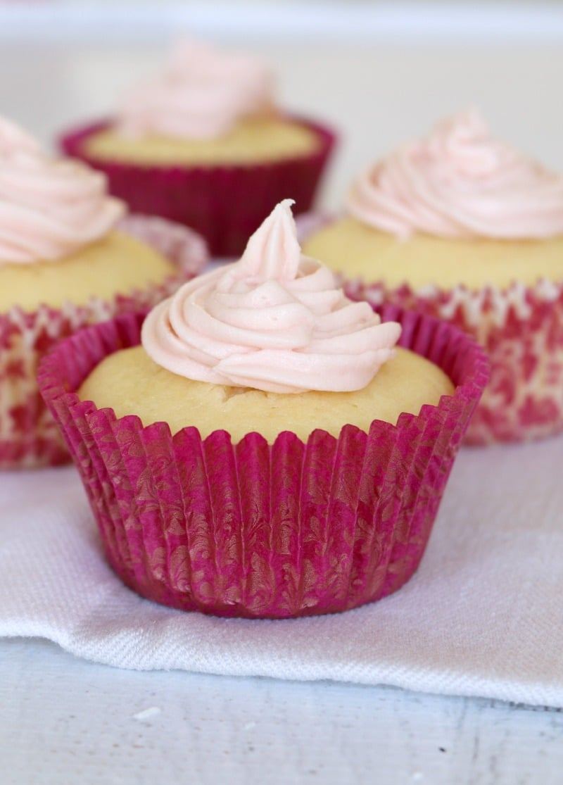 Lemon cupcakes with white frosting in pink cupcake cases