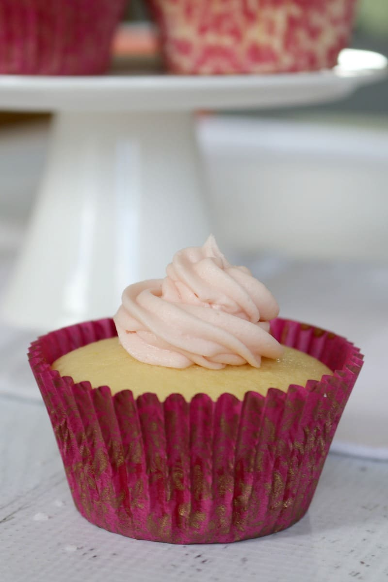 A swirl of white frosting on top of a lemon cupcake in a pink case