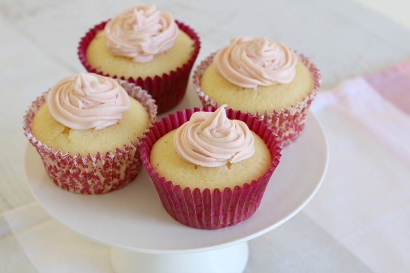 Four lemon cupcakes in pink cupcake cases with white frosting on top