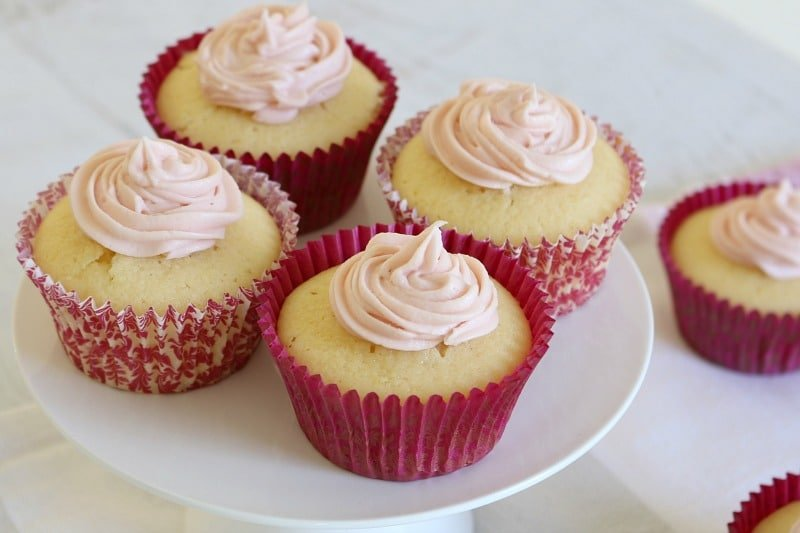 Four cupcakes with swirls of white frosting, and baked in pink cases on a cake stand