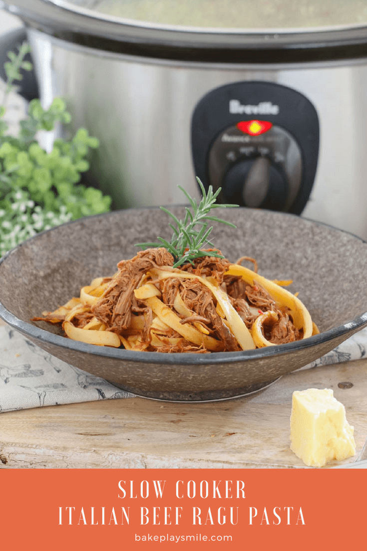 A bowl of rich beef ragu pasta with a slow cooker in the background.