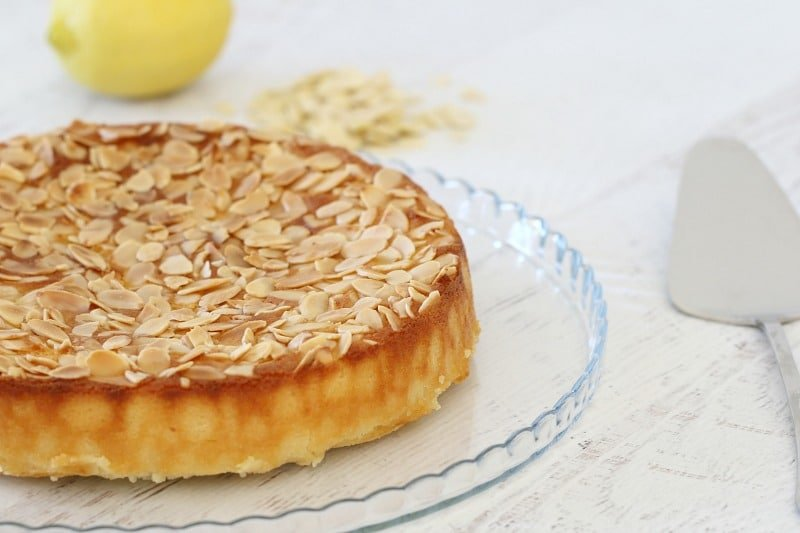 Lemon, ricotta and almond cake served on a clear glass plate