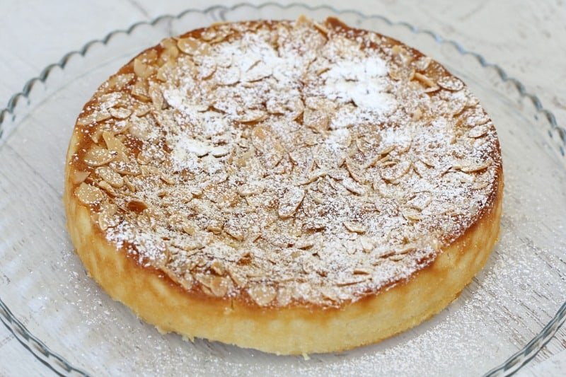 A lemon, ricotta and almond cake dusted with icing sugar, and served on a glass plate
