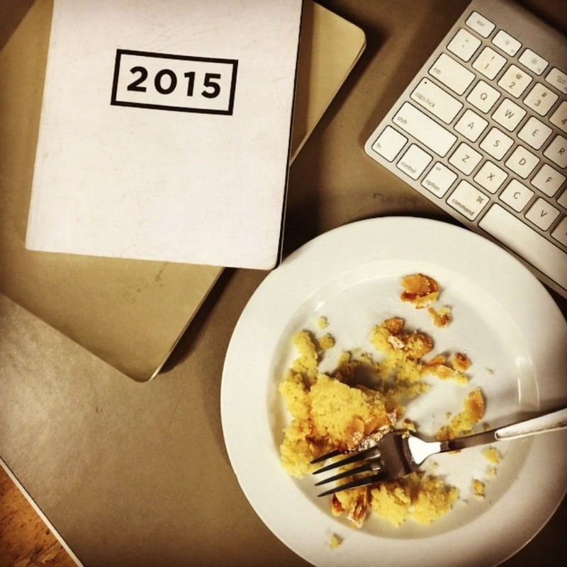 A white plate and fork with a half eaten serve of lemon, ricotta and almond cake next to a keyboard and diary