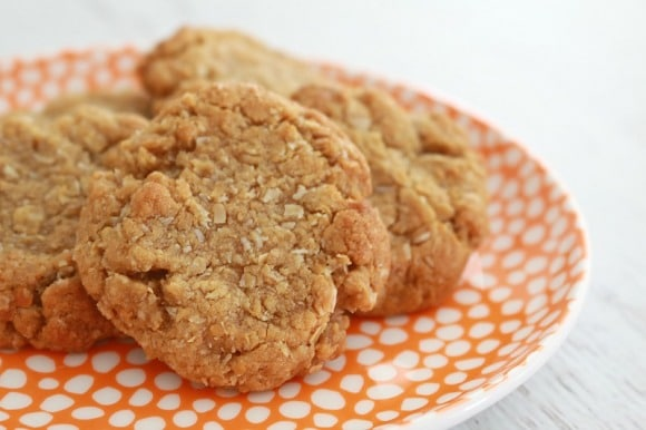A close up of Anzac biscuits made with rolled oats on an orange plate with white dots