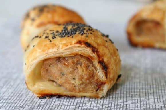 A close up of baked sausage rolls made with chicken and vegetables and sprinkled with poppy seeds