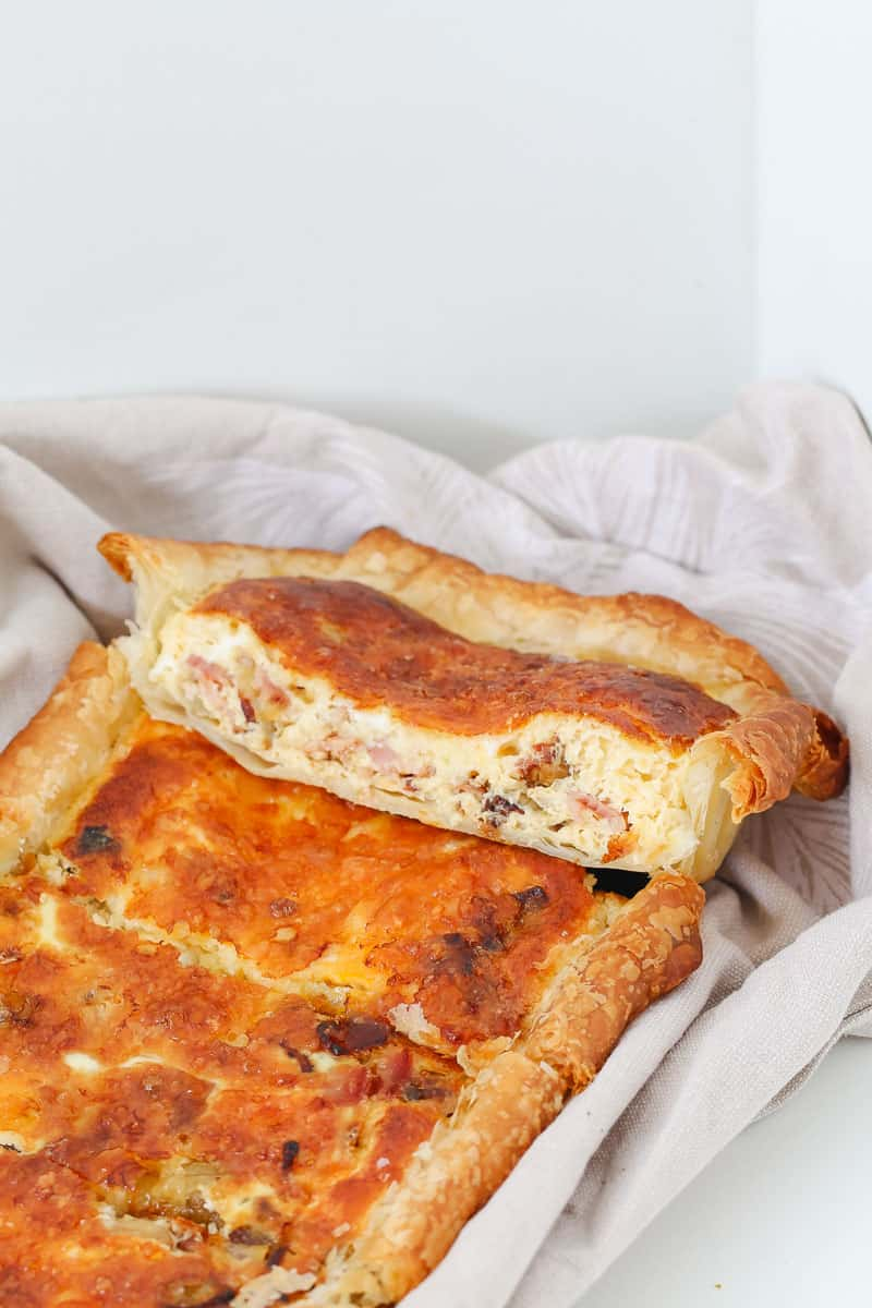A slice of a quiche with a bacon, egg, onion and cheese filling and puff pastry on the outside.