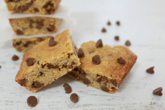 A scattering of chocolate chips around squares of a slice made with chocolate chips, sultanas and oats