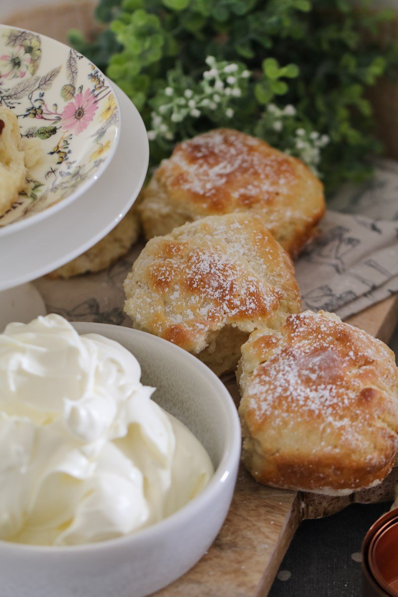 Golden homemade scones sprinkled with icing sugar next to a bowl of whipped cream.