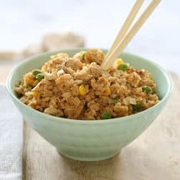 A pale blue bowl filled with fried rice, and a set of chopsticks placed in it