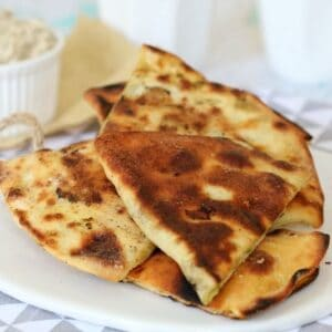 Wedges of baked spinach and feta gozleme piled on a plate