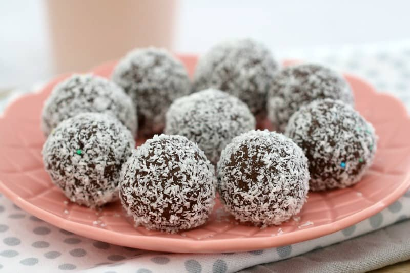 A close up of coconut covered Malteser Balls on a pink plate