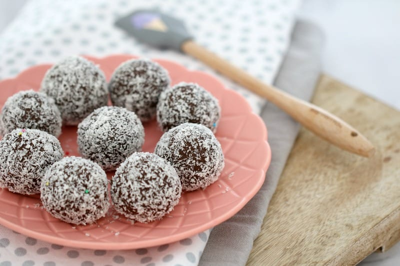 Coconut covered Malteser Balls on a pink plate, with a rubber spatula beside