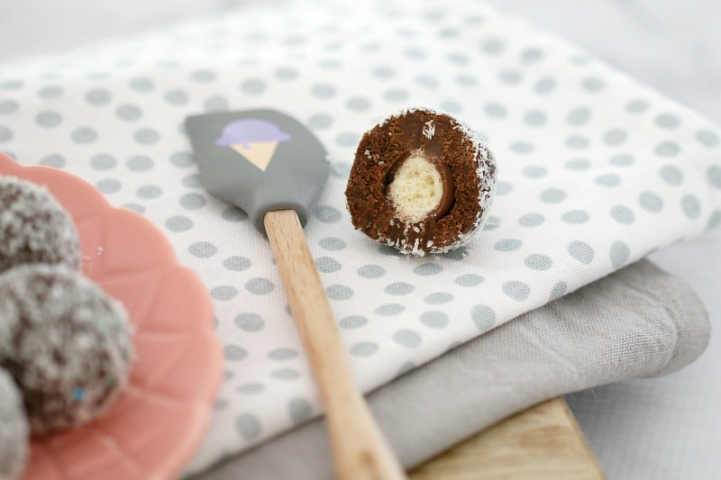 A spit Malteser Ball showing the Malteser inside, resting on a tea towel next to a rubber spatula
