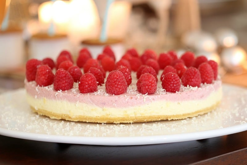 A pink and white layered cheesecake with raspberries on top and sprinkled with grated white chocolate
