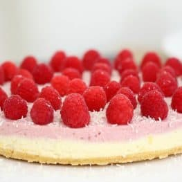 A pink and white layered cheesecake decorated with fresh raspberries and grated white chocolate