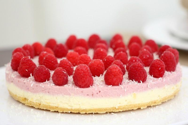 A round no-bake white chocolate and raspberry cheesecake topped with fresh raspberries