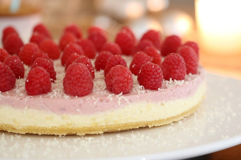 A close up of a no-bake white chocolate and raspberry cheesecake decorated with raspberries and grated white chocolate