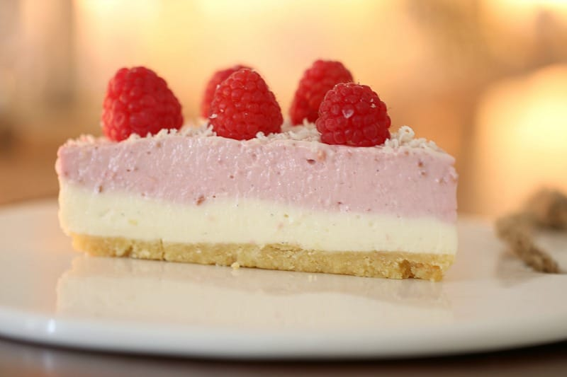 A close up of a slice of cheesecake showing a biscuit crumb, a white layer, then pink layer, and topped with fresh raspberries