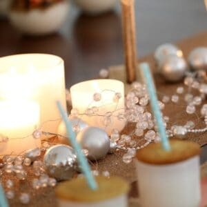 Christmas decorations, candles, and cookies with a straw through them on top of white glass jars