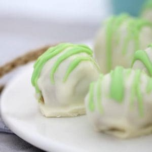 A close up of white chocolate mint balls on a white serving plate