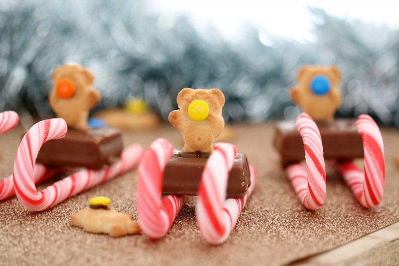 Candy canes under a mini chocolate bite with a Tiny Teddy biscuit on top to resemble a sleigh