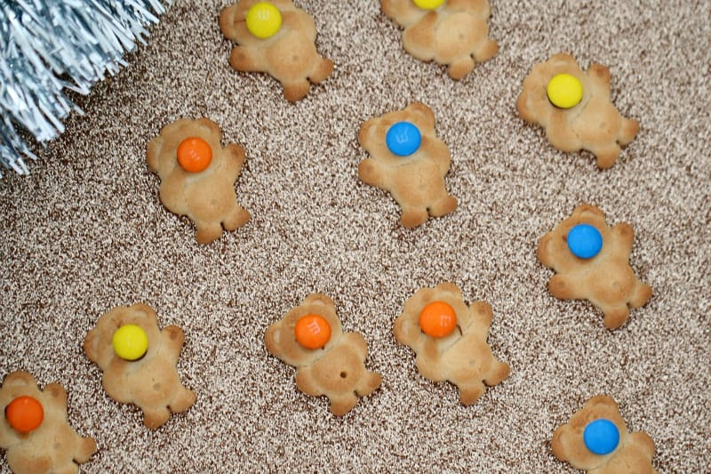 Tiny Teddy biscuits being decorated with coloured Smarties