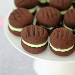 A plate of chocolate cookies sandwiched together with mint cream filling