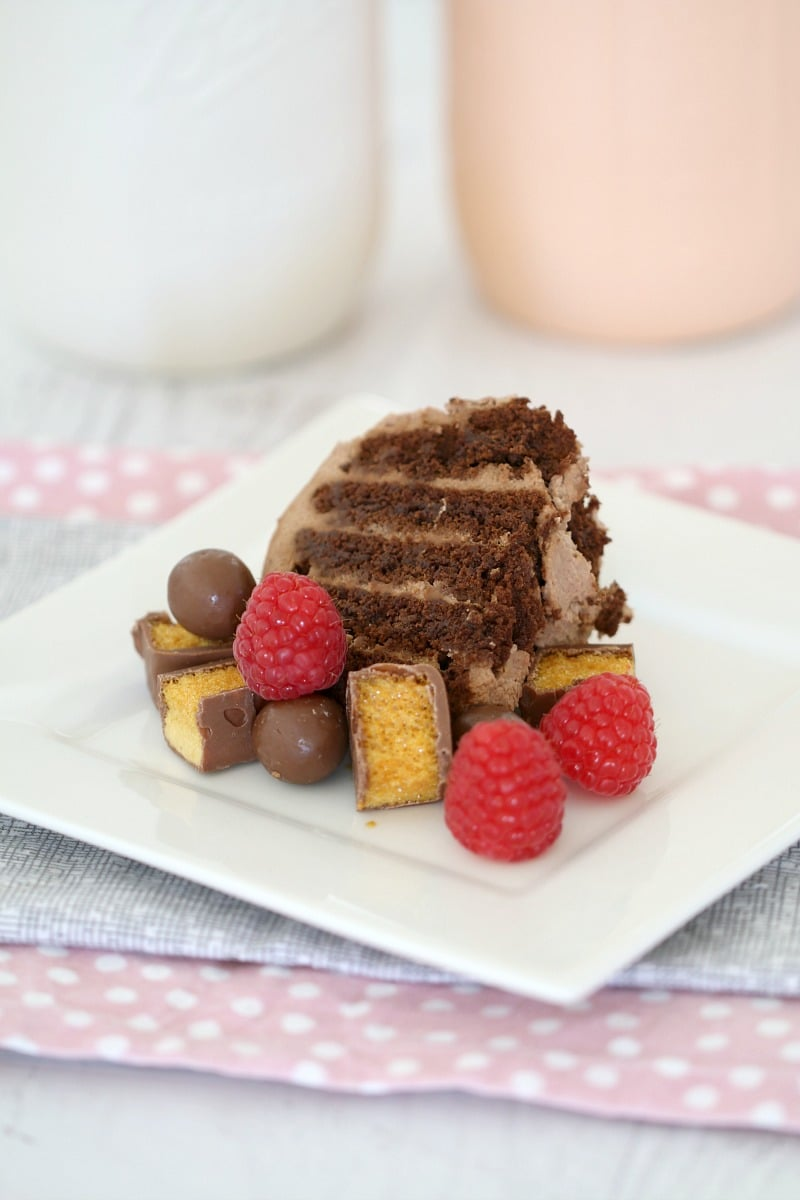 A square white plate with a serve of chocolate ripple cake decorated with raspberries, Maltesers and chopped honeycomb