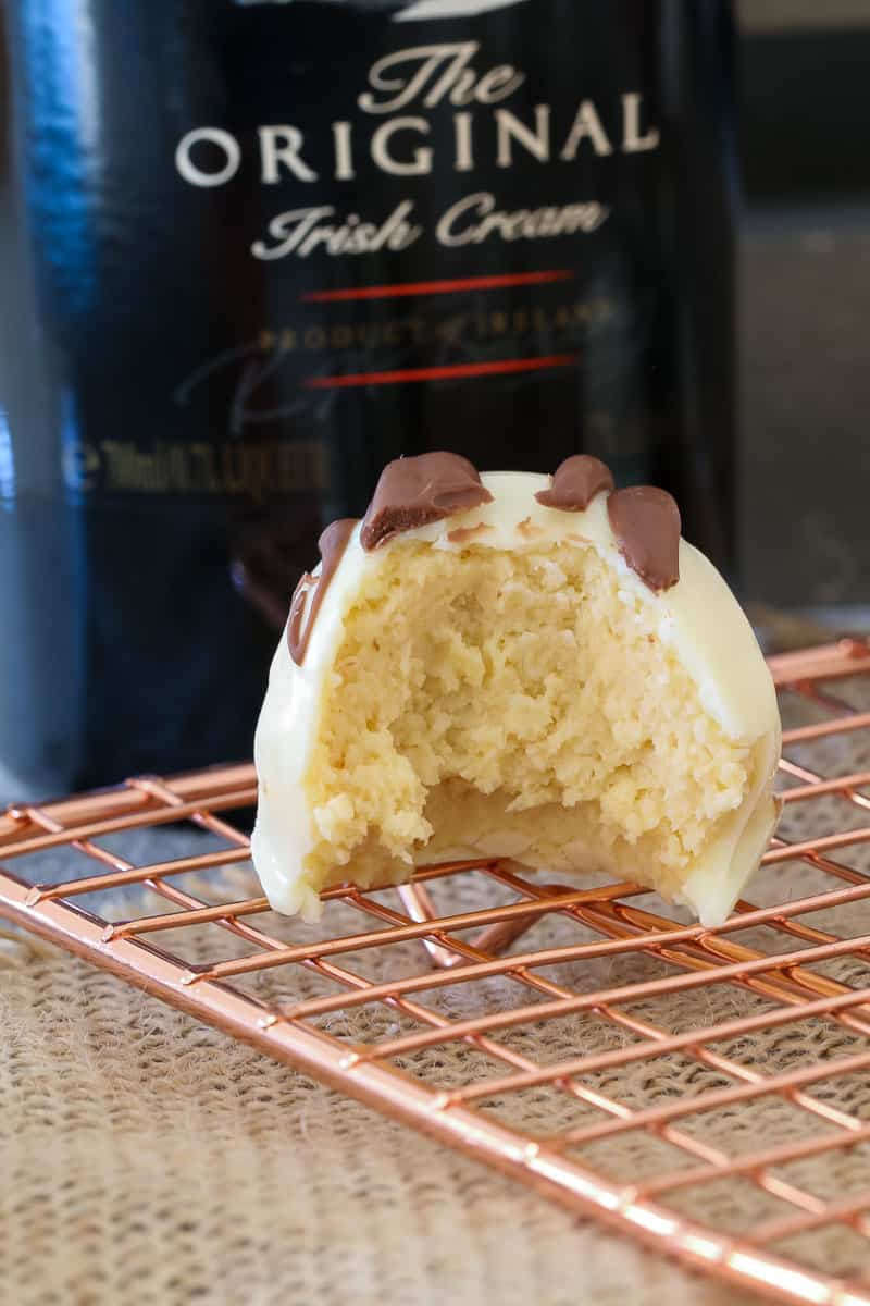 A half-eaten cheesecake ball with a bottle of Baileys Irish cream in the background.