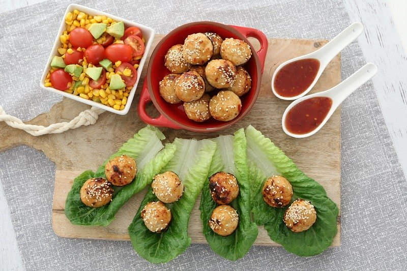 An overhead shot of meatballs, some in a dish, some served on cos lettuce leaves with a dipping sauce and salad ingredients nearby.